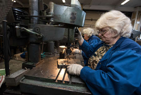 Saint-Petersburg, Russia - March 23, 2016: Women 50-55 years is working on drilling machines in the metalworking shop Editoriali