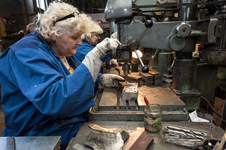 Saint-Petersburg, Russia - March 23, 2016: Women 50-55 years is working on drilling machines in the metalworking shop Editorial