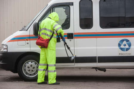 radiation protection suit: Saint-Petersburg, Russia - April 6, 2016: A man in a special protective suit green measures the level of radiation on the car after a decontamination treatment. Editorial