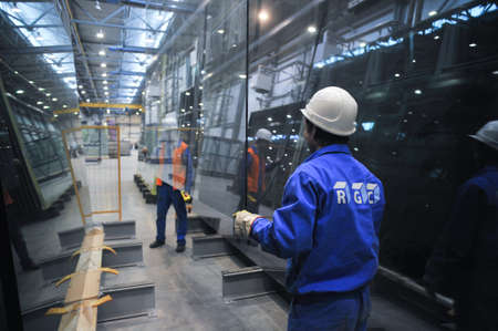 Saint-Petersburg, Russia - 4 February 2010: The float glass production plant. Working professionals monitor the manufacturing process and product quality.