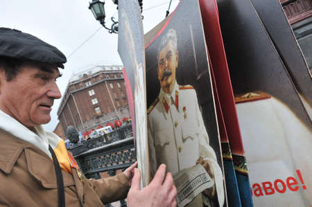 dictator: ST. PETERSBURG, RUSSIA - MAY1: Man with portrait of Soviet dictator Josef Stalin takes part in the May day demonstration in May 1, 2010