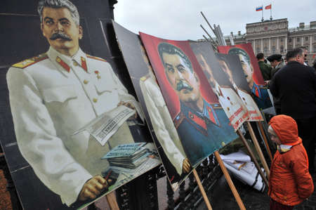 dictator: ST. PETERSBURG, RUSSIA - MAY1: Portraits of Russian dictator Joseph Stalin at the fence of the monument to the Russian Tsar Nicholas 1 during a May Day demonstration in May 1, 2010