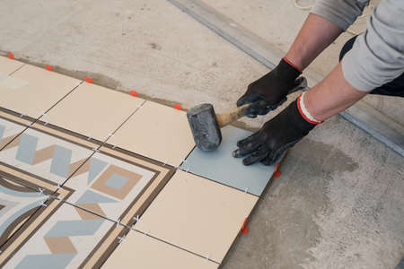 Worker tiler lays tiles. The hands holding the hammer debugging. Living room large apartment. Between the tiles adaptation for smooth clearance. Standard-Bild