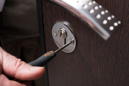spins: Closeup of a Construction worker carpenter fixing screw spins metal safe door Burglar inlaying wood. A hand and a screwdriver in the foreground.