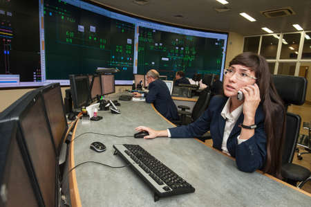 director de escuela: San Petersburgo, Rusia - 22 septiembre 2016: Ingeniero de la mujer joven controla el funcionamiento del sistema de potencia en la administración de energía a distancia de la empresa Editorial