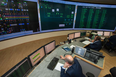 superintendent: Saint-Petersburg, Russia - September 22, 2016: Top view of the office managing the power company. Energy engineers work at computers monitor the city grid.