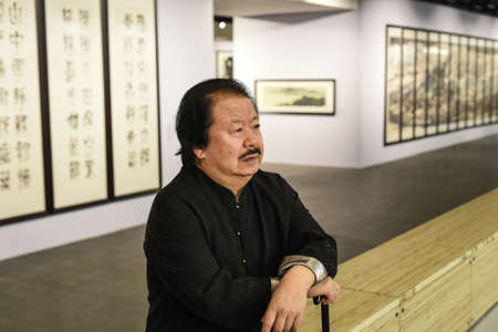 the exhibition hall: Saint-Petersburg, Russia - September 12, 2016: The richest Chinese artist Cui Ruzhuo to the opening of his exhibition in the Central Exhibition Hall on the background of his paintings.