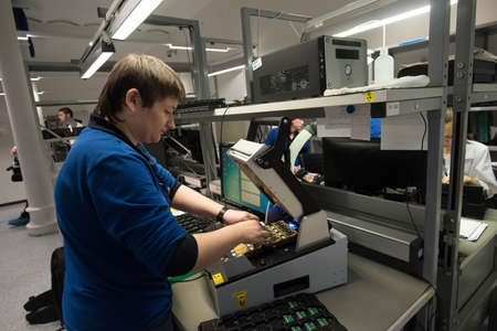 computer equipment: Saint-Petersburg, Russia - November 2, 2016: Manufacturer of automotive security systems Starline. Middle-aged woman specialist inspector is testing the quality of the printed circuit board manufacturing. Editorial