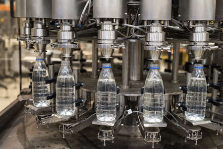 Plastic liter bottles on the assembly line packaging machine pouring. Packing shrink food equipment