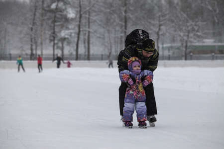 frostily: Saint-Petersburg, Russia - December 2, 2016: Urban outdoor ice rink in the park. Father teaching his child to skate.