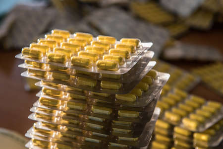 pilule: A large number of blisters capsules, tablets during the packaging production line for pharmaceutical company yellow in sunlight.