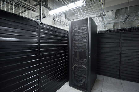 A big data center storage ranges cover and cloud services. Black cabinets in a large room servers.