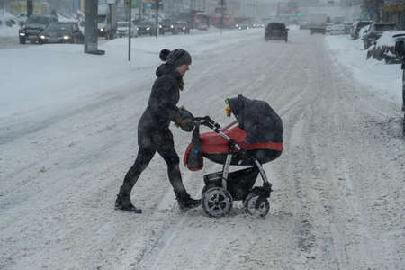 inconvenience: Saint-Petersburg, Russia - November 8, 2016: Snowfall in the city streets. A woman with a baby carriage to cross the carriageway of the road Editorial