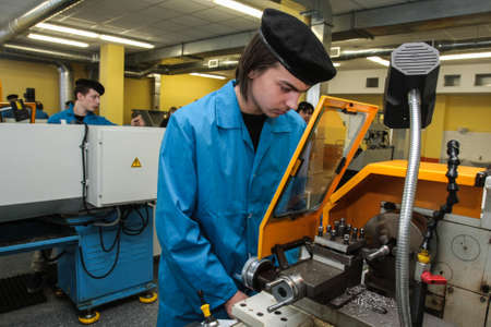technical department: Saint-Petersburg, Russia - February 16, 2012: Students of the vocational school is working on a lathe in the workshop machine factory during manufacturing practices