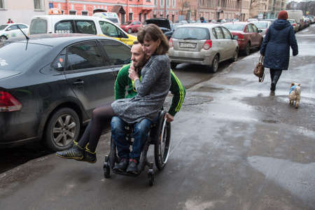 incapacity: Saint-Petersburg, Russia - February 18, 2017: A handsome disabled young man  in a wheelchair with  girl on the street