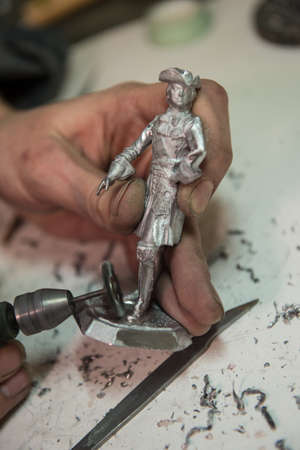 Saint-Petersburg, Russia - February 21, 2017: A small factory producing small batches pewter figurines. The master cleanse warrior figurine from burrs
