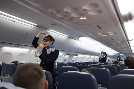 St. Petersburg, Russian Federation - October 16, 2017:  Stewardesses  in the cabin of the 737-800 passenger airplane instruct passengers on safety measures and  in the event of an emergency