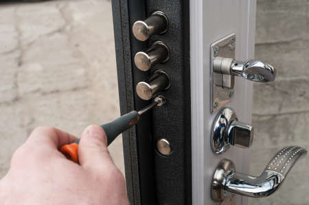 The carpenter installs a reliable burglar-resistant lock in the metal door. Stockfoto