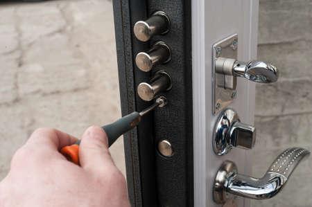 The carpenter installs a reliable burglar-resistant lock in the metal door. Archivio Fotografico