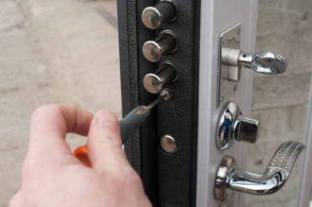 The carpenter installs a reliable burglar-resistant lock in the metal door. Stock Photo