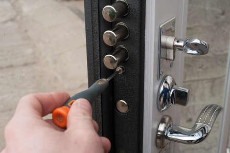 The carpenter installs a reliable burglar-resistant lock in the metal door. 写真素材