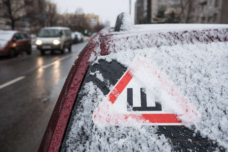 Car sticker on the rear snow-covered glass of the car warning drivers that the car is fitted with wheels with studded rubber Stock Photo