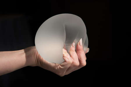 Demonstration of the properties of elasticity, softness, strength, reliability of silicone breast implant, used in plastic surgery to increase or enhance sexuality, aesthetic appeal of forms Foto de archivo