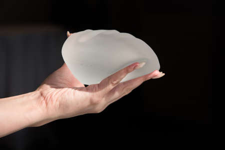 Demonstration of the properties of elasticity, softness, strength, reliability of silicone breast implant, used in plastic surgery to increase or enhance sexuality, aesthetic appeal of forms Stockfoto