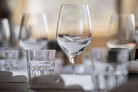 In the restaurant there are wine glasses in the , cutlery, napkins and other items for food, arranged by the catering service on a large table covered with white scarette Foto de archivo