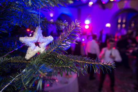 Festive Christmas party. In the foreground there are decorated branches of the New Year tree. In blurring - people dance and have fun Stock Photo