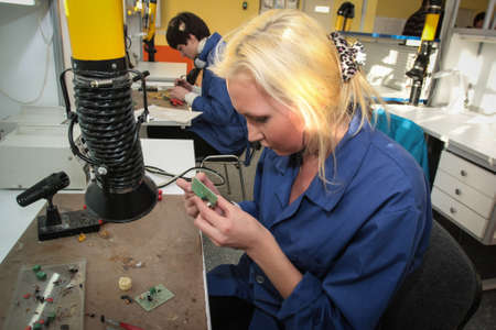 St. Petersburg, Russia - February 16, 2012: Electrotechnical College of Municipal Economy. The girl is repairing the microcircuit Éditoriale