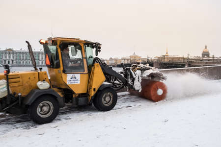 St. Petersburg, Russia - January 1, 2018: Snow removal from the pedestrian sidewalk by a rotating tractor brush in the historical center of the city on the Neva River embankment.