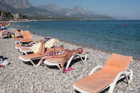 Kemer, Turkey - October 22, 2017: Tourists are resting on the beach of Kemer. Free sunbed in the foreground.