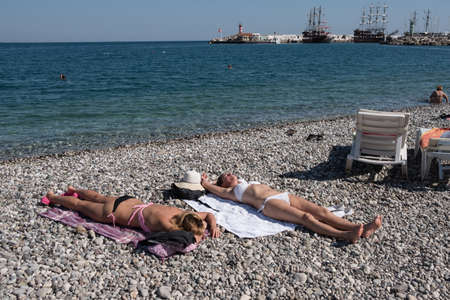 Kemer, Turkey - October 22, 2017: Tourists are resting on the beach of Kemer. two Girls lie on pebbles on towels Editorial