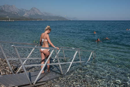 Kemer, Turkey - October 22, 2017: Tourists are resting on the beach of Kemer. Beautiful young girl enters the water.