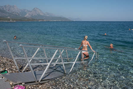 Kemer, Turkey - October 22, 2017: Tourists are resting on the beach of Kemer. In the foreground, a special path for entering the water