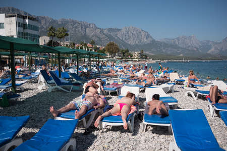 Kemer, Turkey - October 22, 2017: Tourists are resting on the beach of Kemer. View of the beach, hotel and mountains.