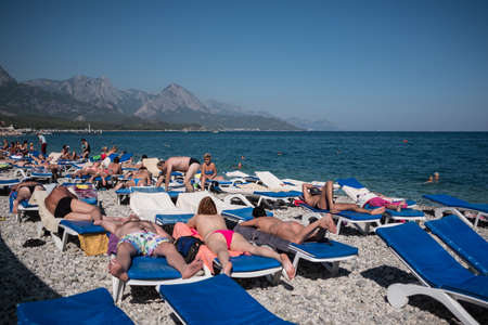 Kemer, Turkey - October 22, 2017: Tourists are resting on the beach of Kemer. Adult men and women sunbathe on sun loungers