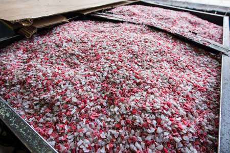 Plastic colored granulated crumb at the plant for processing and casting products from domestic and industrial waste. Ready for loading in the machine for remelting and manufacturing parts