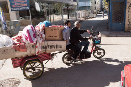 Antalya, Turkey - October 18, 2018: Two men on an electric bike carry personal belongings in a trailer on a city street on a sunny day. Editorial