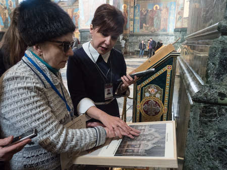 """St. Petersburg, Russia - March 21, 2018: a new excursion route specially for people with visual disabilities in the state museum """"Savior on Blood"""". The guide shows the blind woman exhibits."""