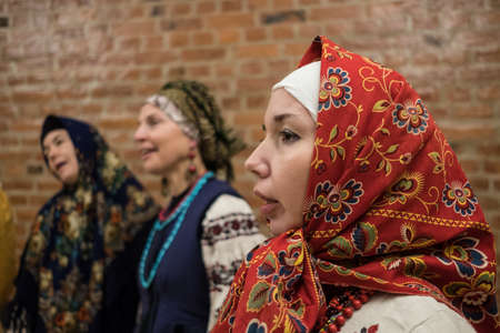 St. Petersburg, Russia - December 17, 2017: A small group of middle-aged women in national costumes is taught singing with the help of a music teacher.
