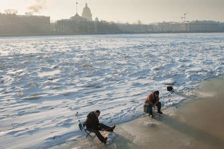 St. Petersburg, Russia - February 15, 2012: Panorama of the Neva - English and Admiralty embankment. In the foreground: fishermen catch a smelt of smelt from under the ice.