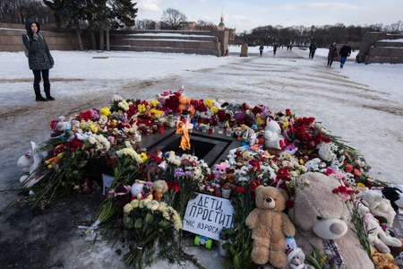 St. Petersburg, Russia -28 March 2018: Flowers and childrens toys are laid to eternal fire on the Champ de Mars on the day of mourning and tragedy in Kemerovo, where people died in the Winter Cherry mall