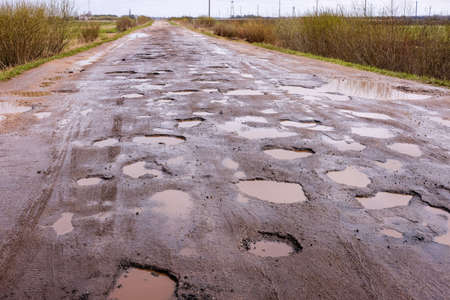 Road with lots of potholes, filled with rain. Bad condition of covering the highway, dangerous for traffic Stock Photo