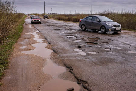 Novgorod Region, Russia-May 1, 2018: The road of local importance in emergency condition with a lot of potholes flooded with rain. Cars go with the risk of breakdowns Redakční