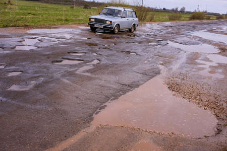 Novgorod Region, Russia-May 1, 2018: The road of local importance in emergency condition with a lot of potholes flooded with rain. Cars go with the risk of breakdowns Editoriali
