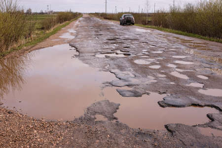 Novgorod Region, Russia-May 1, 2018: The road of local importance in emergency condition with a lot of potholes flooded with rain. Cars go with the risk of breakdowns Editorial