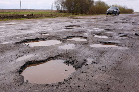 Novgorod Region, Russia-May 1, 2018: The road of local importance in emergency condition with a lot of potholes flooded with rain. Cars go with the risk of breakdowns Редакционное