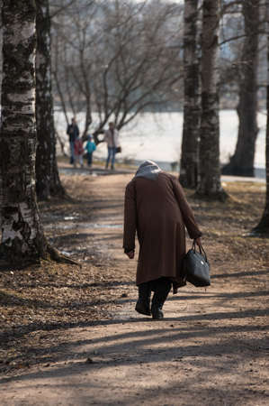 An unrecognizable old bent woman walks along an autumn alley. As a symbol of old age and life. In the hands of her bag. On head scarf. Unstable skewed gait. Archivio Fotografico